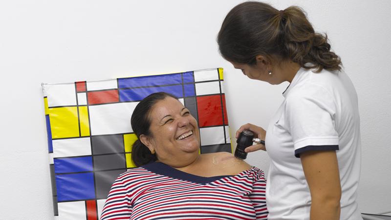 Técnica de reabilitação a tratar ombro a mulher