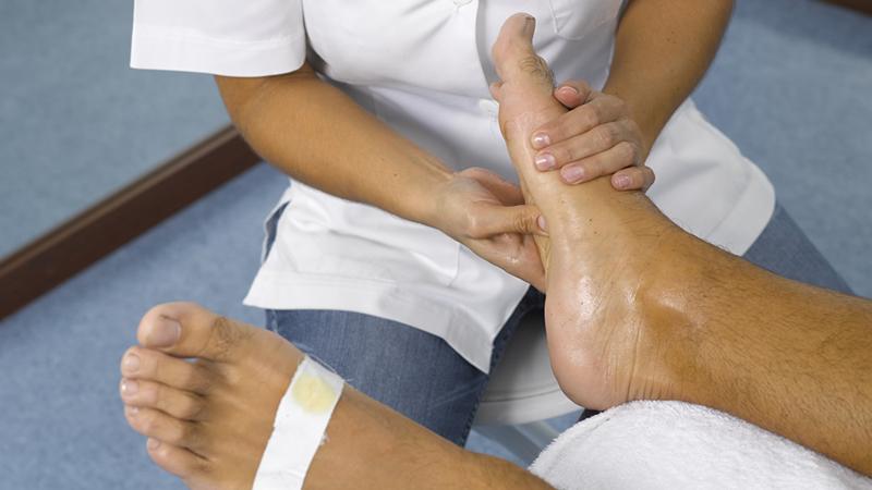 técnica de fisioterapia a massager o pé de um paciente
