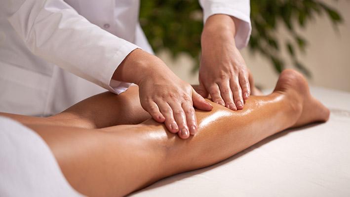 técnica de fisioterapia a massager perna de uma paciente